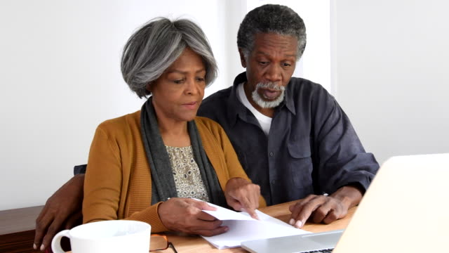 senior african american couple discussing home finances - home finances stock videos & royalty-free footage