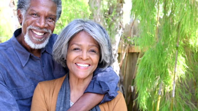 Senior African American couple embracing, looking towards camera