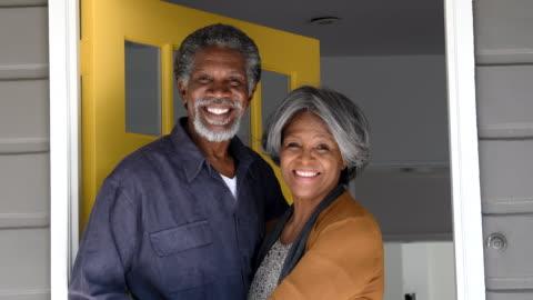 vidéos et rushes de couple senior afro-américain dans la porte, souriant - 65 69 ans