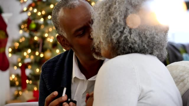 Senior African American couple kissing after exchanging Christmas gifts