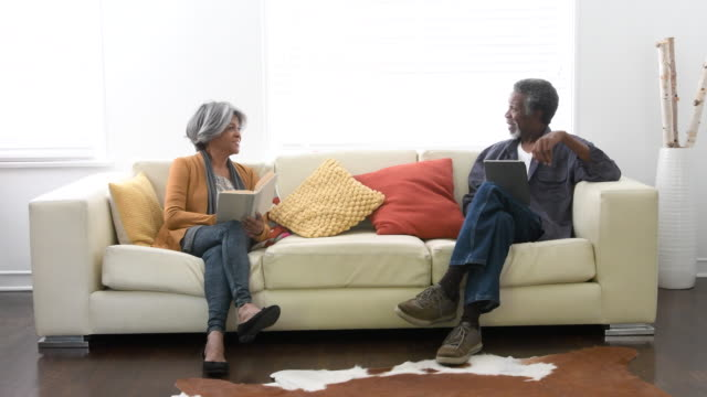 senior african american couple on sofa, man showing tablet - 60 64 anni video stock e b–roll