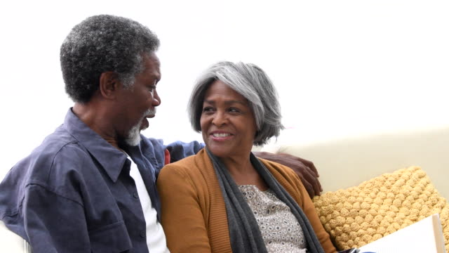 Senior African American couple on sofa smiling and laughing