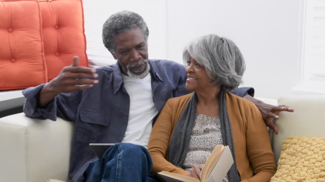senior african american couple on sofa talking affectionately - 60 69 years stock videos & royalty-free footage