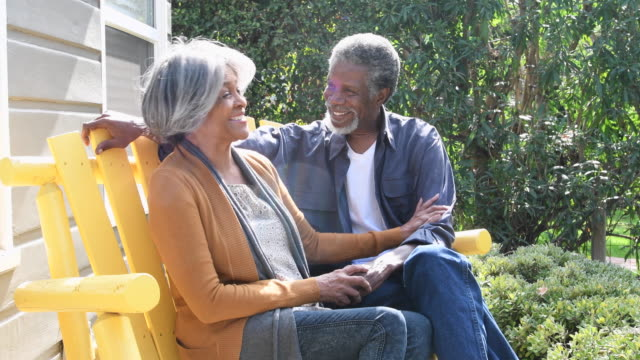 Senior African American couple sitting on chairs outside, laughing