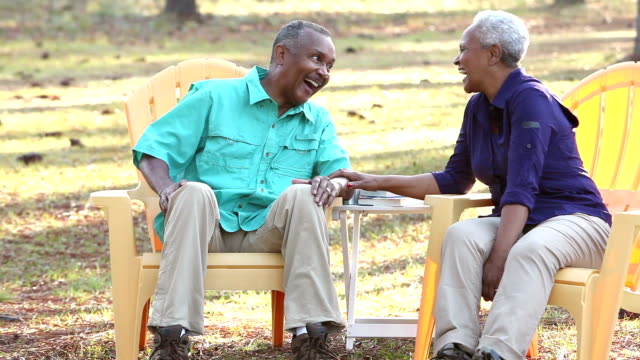 senior african american couple sitting outdoors, talking - outdoor chair stock videos & royalty-free footage