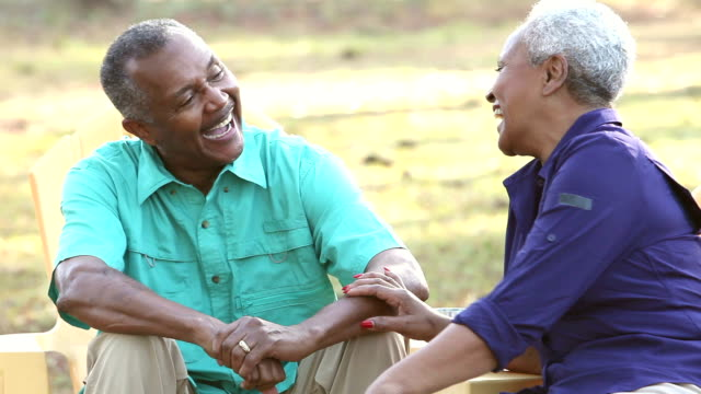 Senior African American couple sitting outdoors, talking