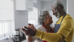 A senior african american couple spending time together at home dancing in the kitchen social distan