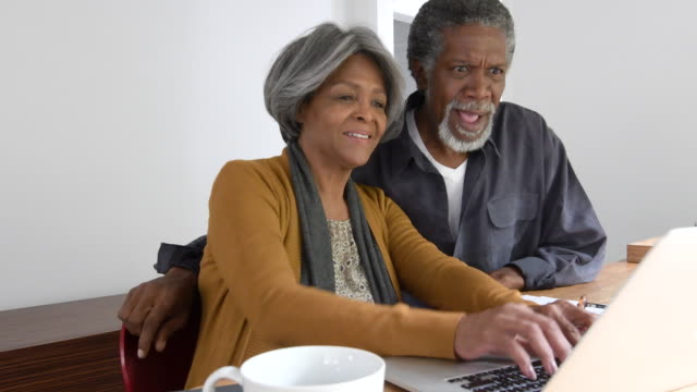 senior african american couple using laptop at home - 60 69 years stock videos & royalty-free footage