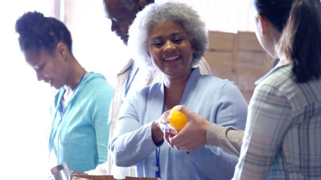 Senior-African-American-Food Bank Freiwillige erhält gespendeten Lebensmittel