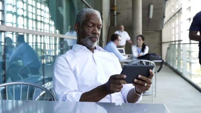 senior african american male doctor using a digital tablet to check patient schedule - canteen stock videos & royalty-free footage