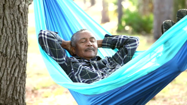 Senior African American man taking nap in hammock