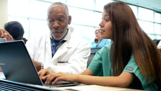 senior african american professor tutoring nursing or medical student in class - lecture hall stock videos & royalty-free footage