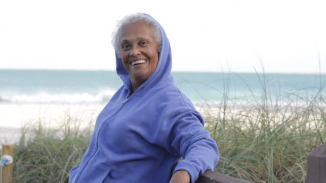 senior african american woman at beach - hooded top stock videos & royalty-free footage