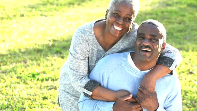 Senior African American woman cheers up sad husband