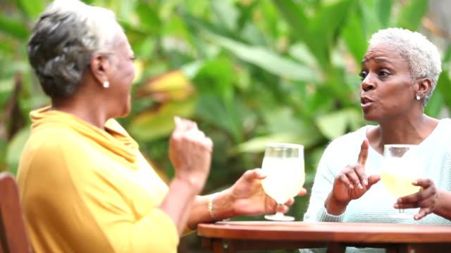 シニア アフリカ系アメリカ人女性の会話、飲酒 - パティオ点の映像素材/bロール