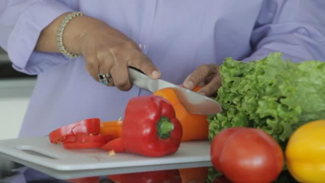 senior african american woman cutting vegetables - オレンジピーマン点の映像素材/bロール
