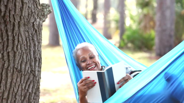senior african american woman reading in hammock - hammock stock videos & royalty-free footage