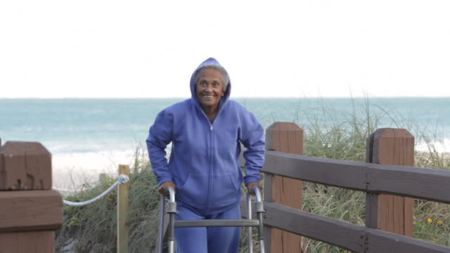 senior african american woman with walker at beach - vulnerability stock videos & royalty-free footage