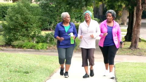 senior african american women power walking, talking - three people stock videos & royalty-free footage