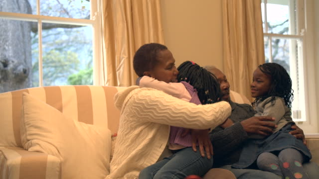 MLS senior African couple sitting on sofa as grandchildren run towards them/ Cape Town/ South Africa