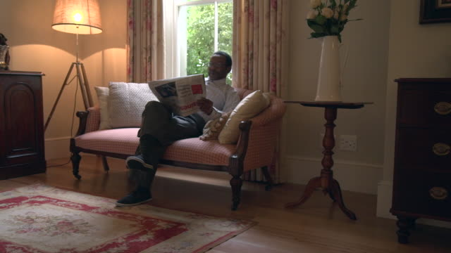 ls senior african man sitting reading newspaper/ cape town/ south africa - 60代点の映像素材/bロール