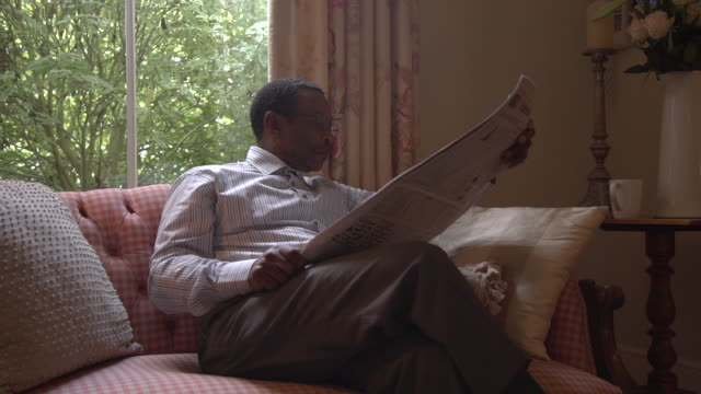 ms senior african man sitting reading newspaper/ cape town/ south africa - newspaper stock videos & royalty-free footage