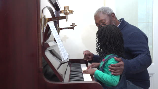 ms senior african man teaching grandchild to play piano/ cape town/ south africa - bib overalls stock videos and b-roll footage