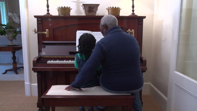 stockvideo's en b-roll-footage met mls senior african man teaching grandchild to play piano/ cape town/ south africa - dreadlocks