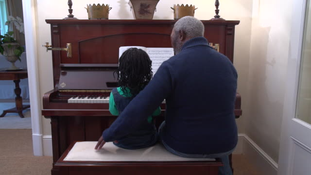 MLS senior African man teaching grandchild to play piano/ Cape Town/ South Africa