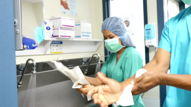 Senior African surgeon and Asian nurse dry hands in preparation of surgery