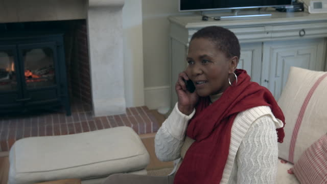 stockvideo's en b-roll-footage met ms senior african  woman sitting by fireplace using mobile phone/ cape town/ south africa - alleen één oudere vrouw