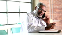 Senior African-American businessman on phone takes notes
