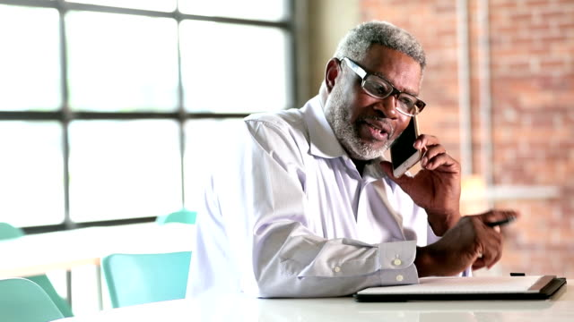 senior african-american businessman on phone takes notes - usare il telefono video stock e b–roll