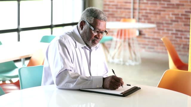 vidéos et rushes de homme d'affaires senior afro-américaine s'assied et écrit - 60 64 ans
