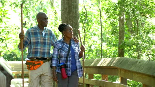 stockvideo's en b-roll-footage met senior afro-amerikaanse paar wandelen in de bossen - 70 79 jaar
