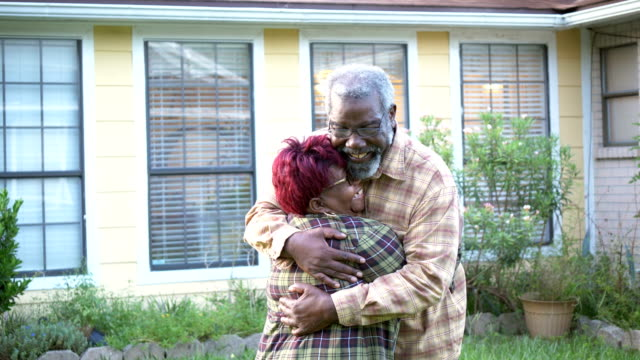 senior african-american couple hugging in front of home - plaid shirt stock videos & royalty-free footage