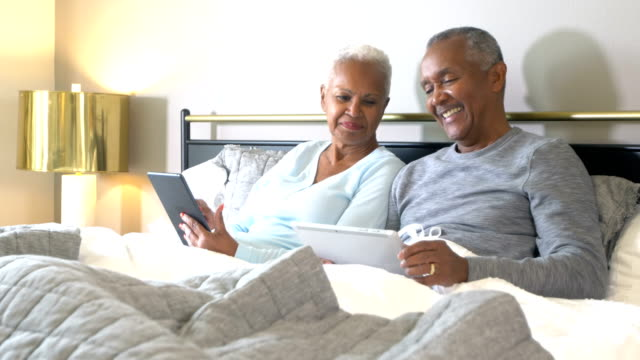 senior african-american couple reading in bed - 60 69 years stock videos & royalty-free footage