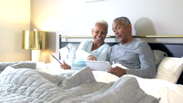 senior african-american couple reading in bed - e book stock videos & royalty-free footage