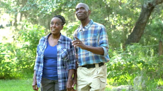 vídeos de stock e filmes b-roll de senior african-american couple walking exploring park - african american ethnicity