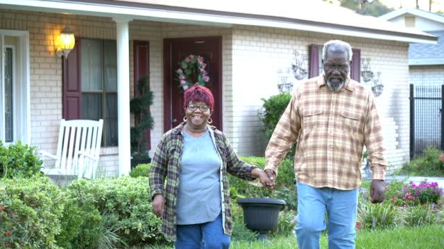 家の前を歩くアフリカ系アメリカ人の上級カップル - 前にいる点の映像素材/bロール