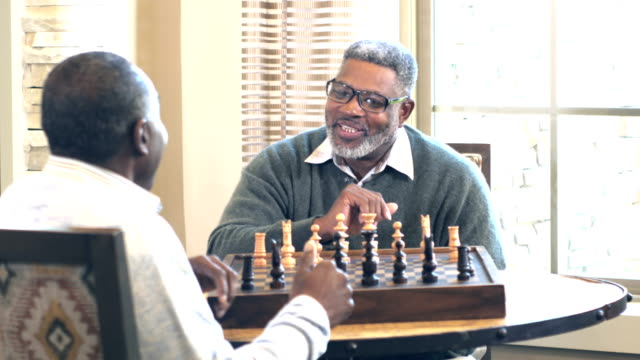 senior african-american man and friend  playing chess - community centre stock videos & royalty-free footage