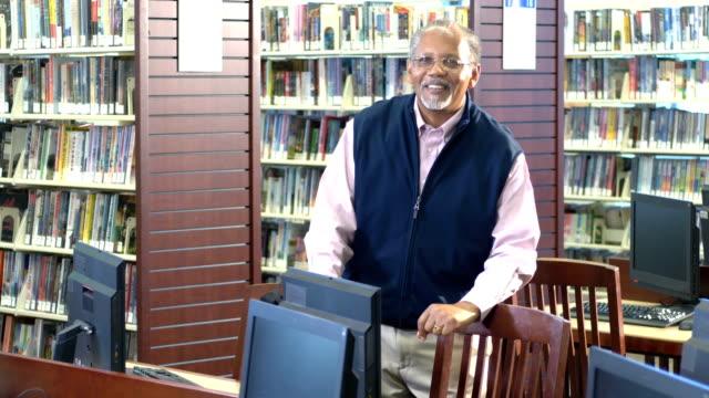 senior african-american man in library - shoulder bag stock videos & royalty-free footage