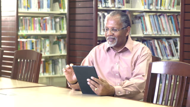 senior african-american man reading in library - e book stock videos & royalty-free footage