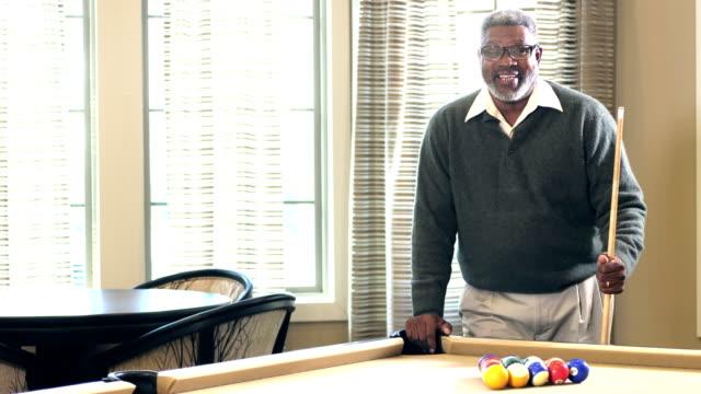 シニア アフリカ系アメリカ人男性のプールを撮影する準備ができて - ビリヤード点の映像素材/bロール