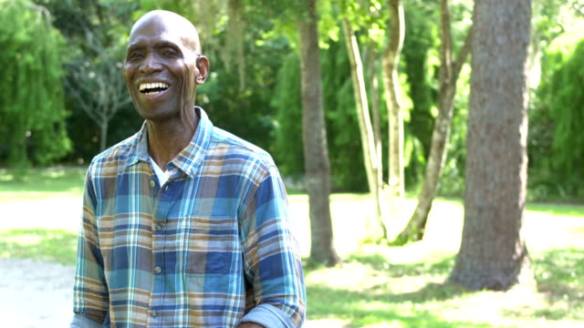 senior african-american man standing outdoors at park - plaid shirt stock videos & royalty-free footage