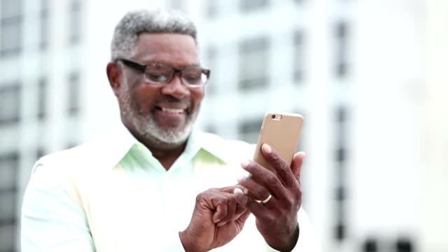vídeos de stock, filmes e b-roll de mandava um homem africano-americano senior telefone móvel - dispositivo de informação portátil