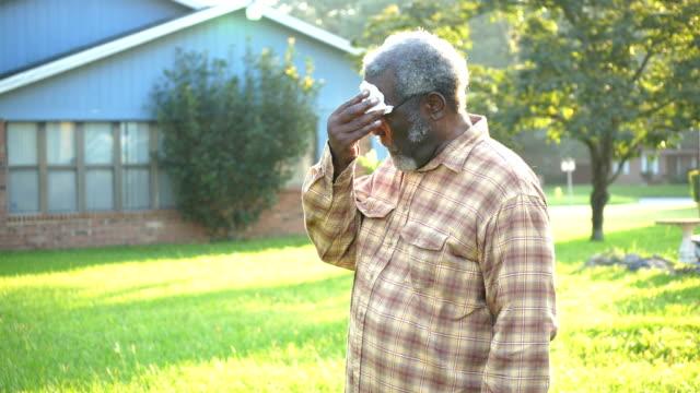 stockvideo's en b-roll-footage met hogere afrikaans-amerikaanse mens die gezicht met weefsel afveegt - 70 79 jaar