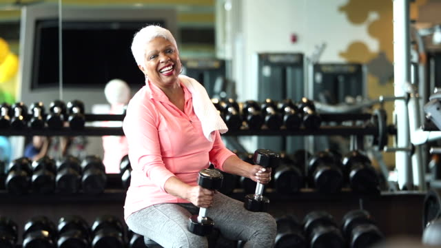 Senior African-American woman at gym, holding dumbbells