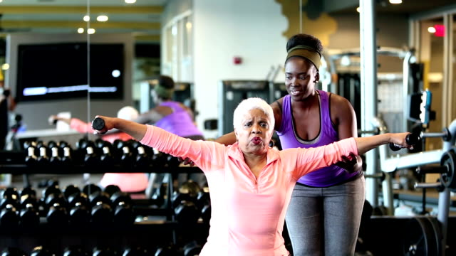 senior african-american woman at gym, personal trainer - weight training stock videos & royalty-free footage