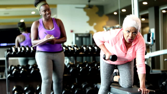 senior african-american woman at gym, personal trainer - hand weight stock videos & royalty-free footage